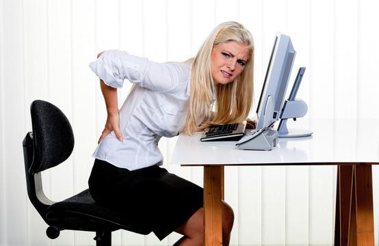 Ergonomic and Chiropractic Care - Woman has back pain at the office
