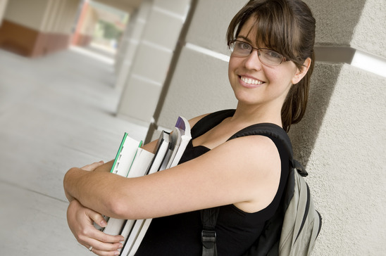 student, holding books, wearing a backpack, outdoors at school